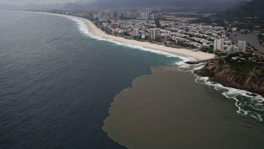 March 23, 2015: This aerial view shows polluted water flowing from the Barra channel to the Barra beach, in Rio de Janeiro, Brazil. (AP Photo/Felipe Dana)