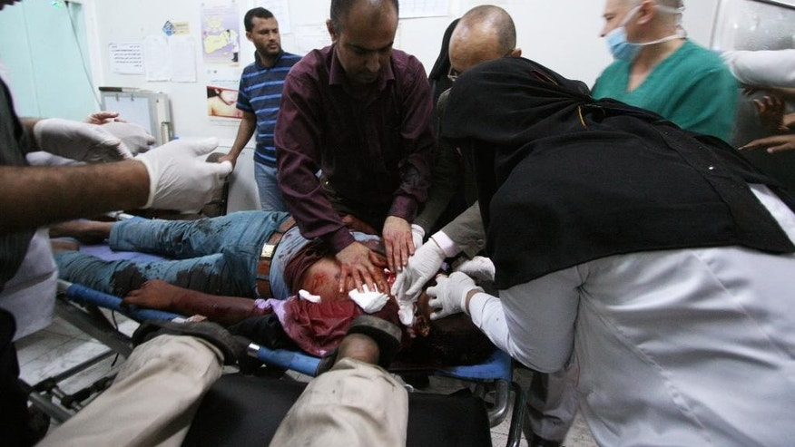 Medics treat an anti-Houthi protester who was injured during clashes with pro-Houthi police troopers in Taiz, Yemen, Tuesday, March 24, 2015. Shiite rebels fired bullets and tear gas to disperse thousands of protesters demanding they withdraw from the southern province, killing six demonstrators, wounding scores more and escalating tensions in a country on the verge of civil war. (AP Photo/Anees Mahyoub)