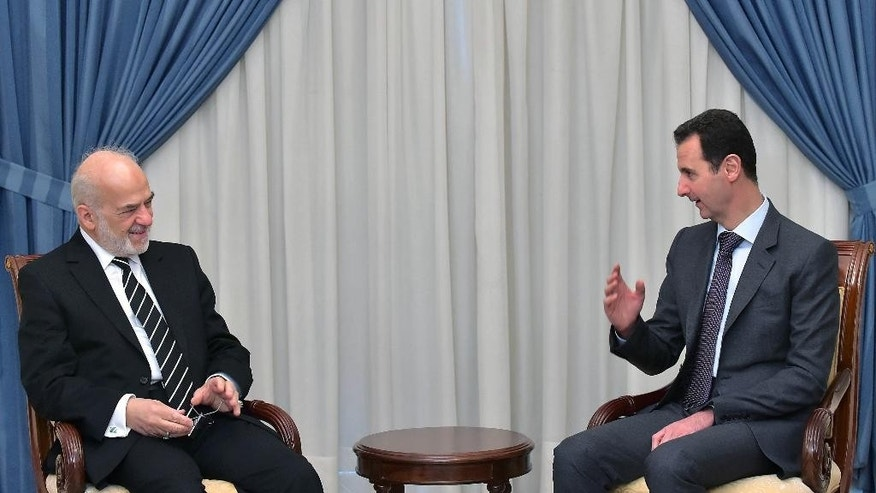 "In this photo released by the Syrian official news agency SANA, Syrian president Bashar Assad, right, speaks with Iraqi Foreign Minister Ibrahim al-Jaafari, left, in Damascus, Syria, Tuesday, March. 24, 2015. Al-Jaafari said they discussed ""Syrian and Iraqi issues, and the common dangers that threaten our security."" (AP Photo/SANA)"