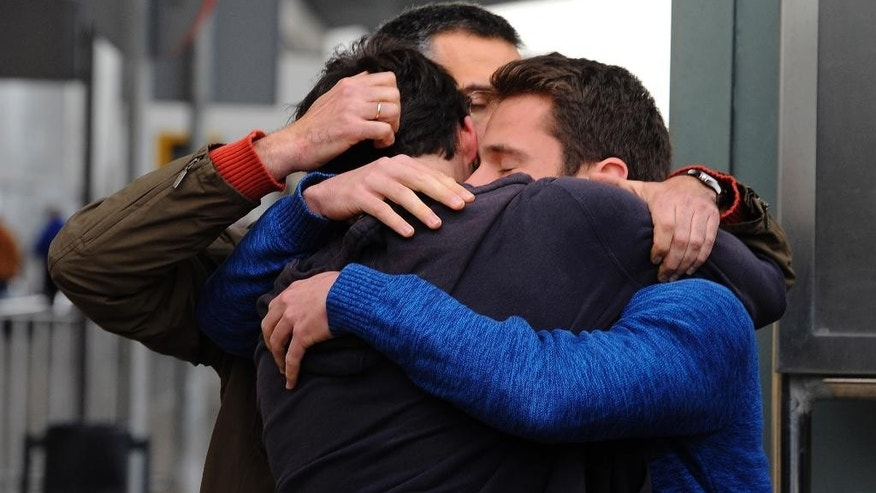 People comfort each other as they arrive at the Barcelona airport in Spain, Tuesday, March 24, 2015. A Germanwings passenger jet carrying 150 people crashed in the French Alps region as it traveled from Barcelona to Duesseldorf in Germany. (AP Photo/Manu Fernandez)