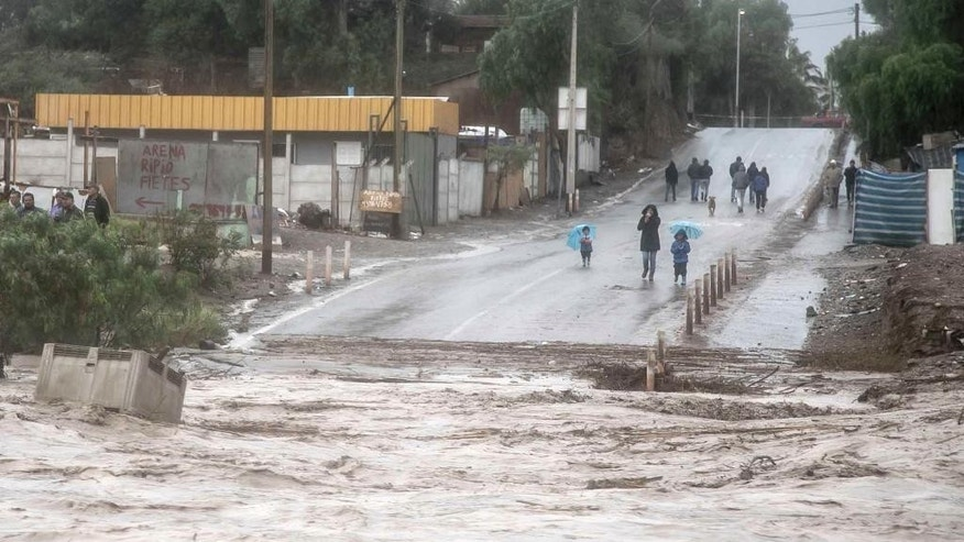 Residents watch the rising flood waters of the Copiapo River, in Copiapo, Chile, Wednesday, March 25, 2015. Unusually heavy thunder storms and torrential rains that began on Tuesday have blocked roads, caused power outages and affected some 600 people on this normally dry region. (AP Photo/Aton Chile)
