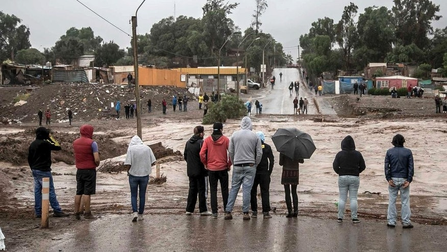 Residents watch the rising flood waters of the Copiapo River, in Copiapo, Chile, Wednesday, March 25, 2015. Unusually heavy thunder storms and torrential rains that began on Tuesday have blocked roads, caused power outages and affected some 600 people on this normally dry region. (AP Photo/Aton Chile) (AP Photo/Aton Chile)