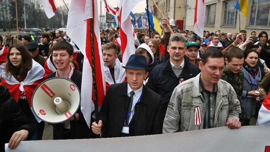 Belarusian opposition protesters shout slogans and wave opposition flags during a rally in Minsk, Belarus, Wednesday, March 25, 2015. March 25 has long been a traditional day of demonstration for the opposition, marking what they call Freedom Day, the anniversary of the 1918 declaration of the first, short-lived independent Belarusian state. (AP Photo/Sergei Grits)