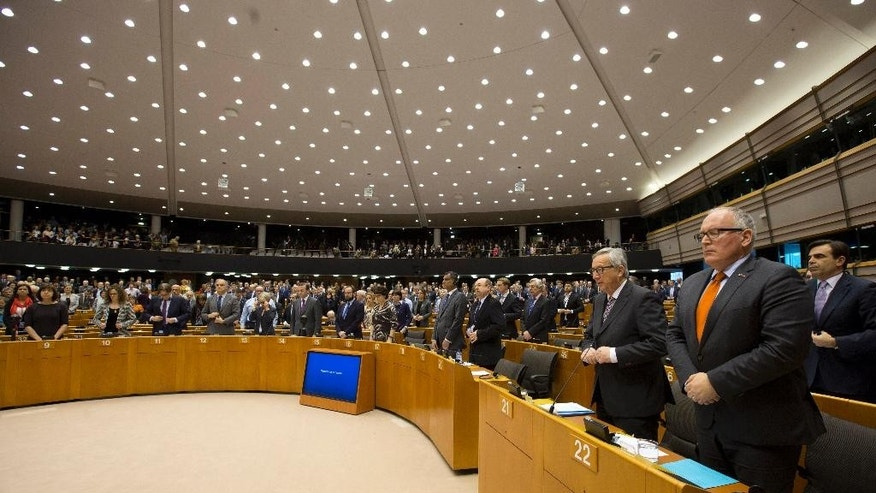 European Commission President Jean-Claude Juncker, front second right, stands with MEP's during a minute of silence at the European Parliament in Brussels on Wednesday, March 25, 2015. The commemoration was held for the victims that died Tuesday in the Germanwings plane crash in the French Alps on the way from Barcelona, Spain to Duesseldorf in Germany. (AP Photo/Virginia Mayo)