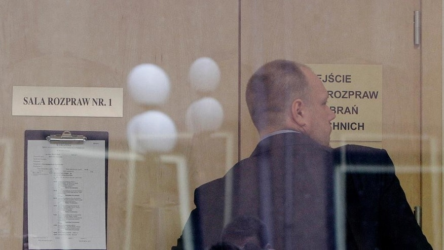 The attorney Michal Szreniawa for former Polish priest Wojciech Gil who is accused of abusing minors in the Dominican Republic and in Poland, enters the courtroom in Wolomin near Warsaw, Poland, on Wednesday, March 25, 2015. The court found Gil, 37, guilty and handed him a seven-year prison term that he had sought in a settlement. (AP Photo/Czarek Sokolowski)
