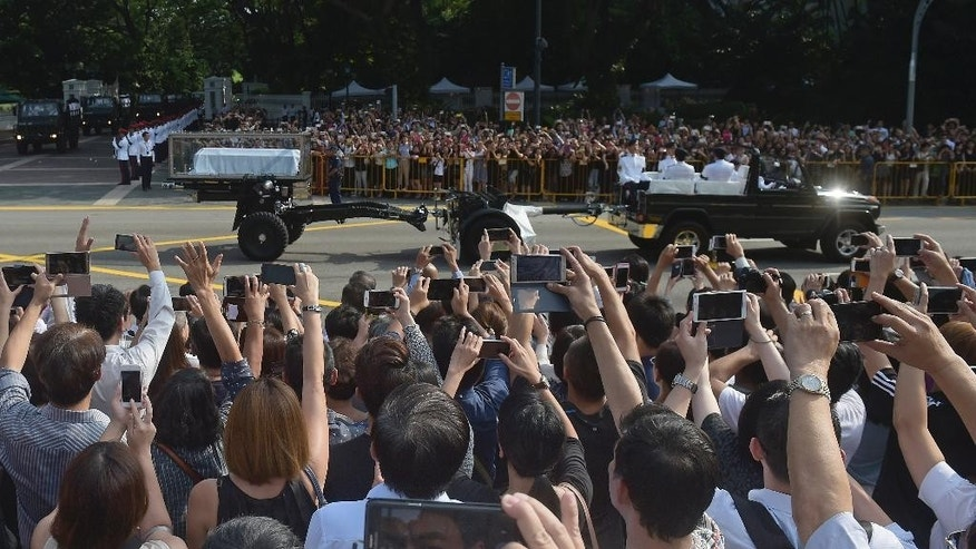 "Members of the public take pictures and shout ""Thank you, Mr Lee!"" as the coffin of Singapore's founding father Lee Kuan Yew leaves Istana, or Presidential Palace on a ceremonial gun carriage to lie in state at parliament, Wednesday, March 25, 2015 in Singapore.  (AP Photo/Joseph Nair)"