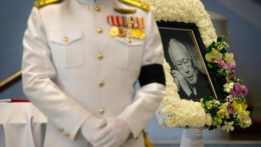 A portrait of the late Lee Kuan Yew is placed at the foot of his coffin where he will lie in state at the Parliament House for four days,  Wednesday, March 25, 2015, in Singapore. Singapore mourned longtime leader Lee with raw emotion and a blanket of relentlessly positive coverage on its tightly scripted state television on Monday, mythologizing a man who was as respected as he was feared. (AP Photo/Wong Maye-E)