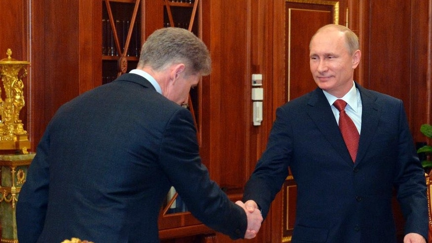 Russian President Vladimir Putin, right, shakes hands with Oleg Kozhemyako, left, a newly appointed acting governor of the Russian Pacific Island of Sakhalin in Moscow, Russia, Wednesday, March 25, 2015. Putin has fired the governor of a far-flung region who has been arrested on charges of corruption. Alexander Khoroshavin, governor of Sakhalin just north of Japan, was arrested earlier this month on suspicion of receiving a bribe for building a power station. (AP Photo/RIA Novosti, Alexei Druzhinin, Presidential Press Service)