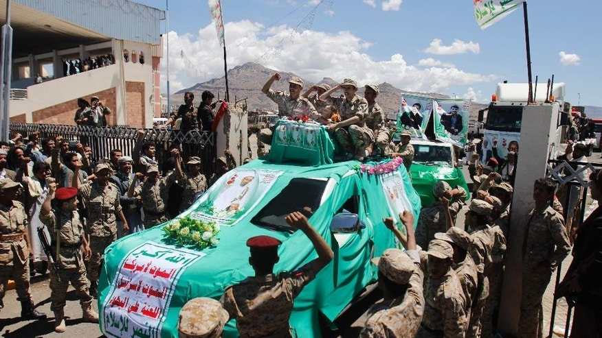 Houthi Shiite fighters wearing an army uniform chant slogans during the funeral procession of victims who were killed last week from triple suicide bombing attacks that hit a pair of mosques in Sanaa, Yemen, Wednesday, March 25, 2015. (AP Photo/Hani Mohammed)