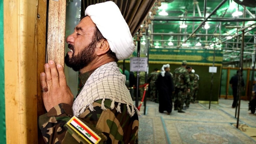 "In this Sunday, March 22, 2015 photo, Sheik Jaber al-Lami, a militia fighter from Baghdad, now based in Samarra, prays inside a Shiite shrine in Samarra, 95 kilometers (60 miles) north of Baghdad, Iraq. ""Daesh consists of 10 percent foreigners and 90 percent residents of the area,"" said al-Lami, using an acronym for the group. ""We're the ones who are defending this city, it's (the Sunnis) who let them come into this area in the first place."" (AP Photo/Karim Kadim)"