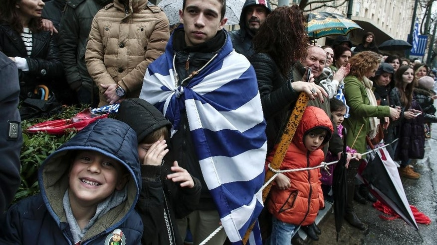 Spectators watch a military parade on Greece's Independence Day, marking the start of the uprising against the Ottomans back in 1821, in Athens, March 25, 2015. Thousands of Greeks have lined a main central Athens avenue despite rain to watch the country's annual Independence Day military parade, with spectators allowed along the route for the first time in about three years. (AP Photo/Panayiotis Tzamaros)