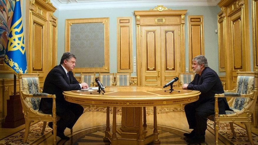 Ukraine's President Petro Poroshenko, left, listens to Ihor Kolomoysky, governor of Dnipropetrovsk, in Kiev, Ukraine, Wednesday, March 25, 2015. Poroshenko has fired the billionaire governor of an eastern region following a rancorous dispute pitting the tycoon against the government. (AP Photo/Mikhail Palinchak, Presidential Press Service)