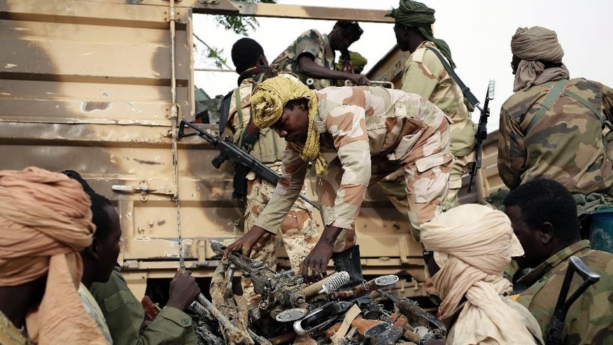 FILE-In this file photo taken on Wednesday March 18, 2015, Chadian soldiers collect weapons seized from Boko Haram fighters  in the Nigerian city of Damasak, Nigeria.  Hundreds of civilians, including many children, have been kidnapped and are being used as human shields by Boko Haram extremists, a top Nigerian official confirmed Wednesday, March 25, 2015. (AP Photo/Jerome Delay, File)