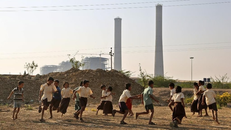 In this Tuesday, Feb. 24, 2015 photo, children play in front of chimneys standing at an under- construction coal-fired power plant, partially financed by the Japan Bank for International Cooperation, in Kudgi, India. Despite mounting protests, Japan continues to finance the building of coal-fired power plants with money earmarked for fighting climate change, with two new projects underway in India and Bangladesh, The Associated Press has found. (AP Photo/Aijaz Rahi)