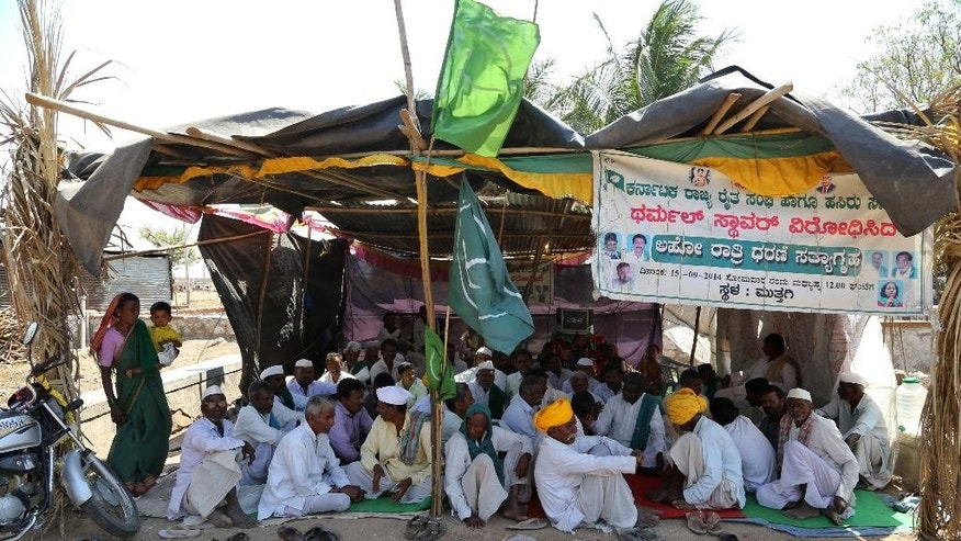 "In this Tuesday, Feb. 24, 2015 photo, farmers and local villagers sit at the site of a protest against the under- construction coal-fired Kudgi power plant, partially financed by the Japan Bank for International Cooperation, in nearby Muttagi, India. Construction of the plant has resumed after coming to a standstill following violent protests last July when police opened fire on angry demonstrators. The protesters have set up a makeshift shed of bamboo sticks and tin sheets and plastic and are focused on the plant's local environmental impact like potential air pollution, rather than its contribution to global carbon emissions. Banner reads the name of organization along with ""Thermal plant protest. Midnight protest and passive political resistance."" (AP Photo/Aijaz Rahi)"