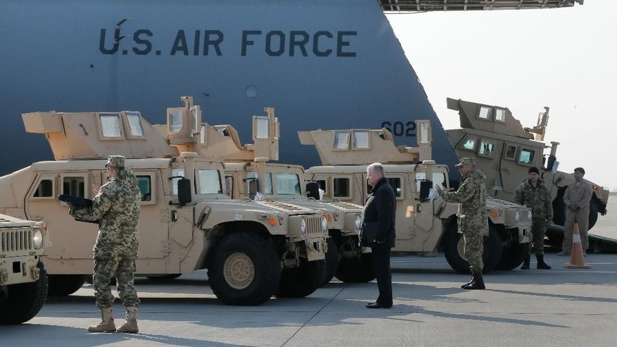The first ten U.S. armored Humvees  for the Ukrainian Army arrive and are unloaded from the U.S. military cargo aircraft in Boryspil Airport, Kiev, Ukraine, Wednesday, March 25, 2015. The U.S. aid for Ukraine's army will include 30 heavily armored Humvees and 200 other regular Humvees, as well as small drones, radios, counter-mortar radars and other equipment. All of the aid is nonlethal, and the drones are not armed. (AP Photo/Efrem Lukatsky)