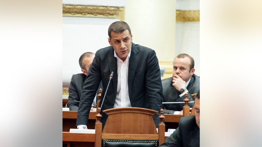 Christian Democratic lawmaker Mark Frroku speaks at the Parliament's session before the vote to lift his and another colleague's immunity, after the latter's claims Speaker Ilir Meta had been behind an assassination plot in Tirana, Thursday, March 26, 2015. Parliament voted in favor of the prosecutors call to arrest Frroku and Tom Doshi, who was expelled from the governing Socialists three weeks ago after the claims.  (AP Photo/Hektor Pustina)