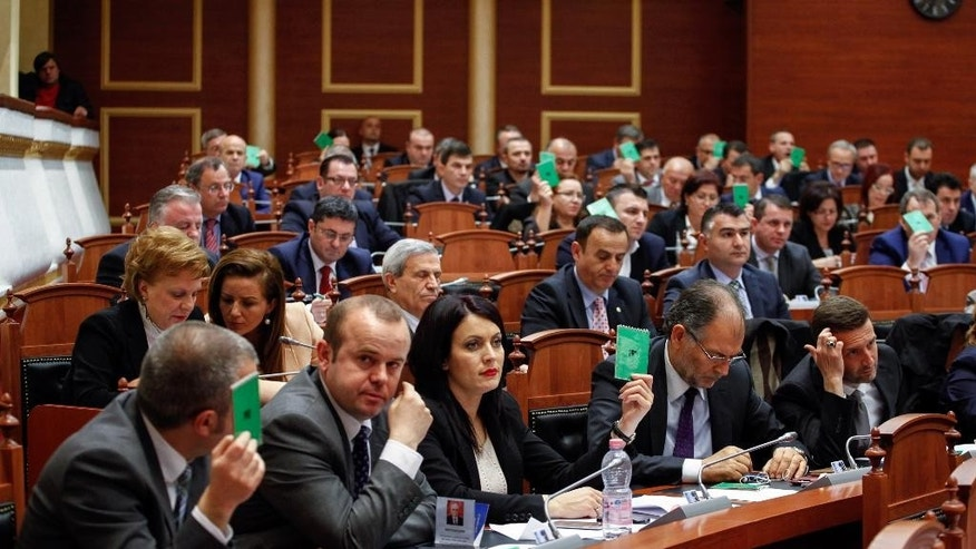 Albania Parliament members vote to lift the immunity of two lawmakers who claimed the Speaker, Ilir Meta, had been behind an assassination plot Tirana, Thursday, March 26, 2015. Parliament voted in favor of the prosecutors' call to arrest Tom Doshi, expelled from the governing Socialists three weeks ago after the claims, and also for Christian Democrat Mark Frroku for false testimony in the case. (AP Photo/Hektor Pustina)