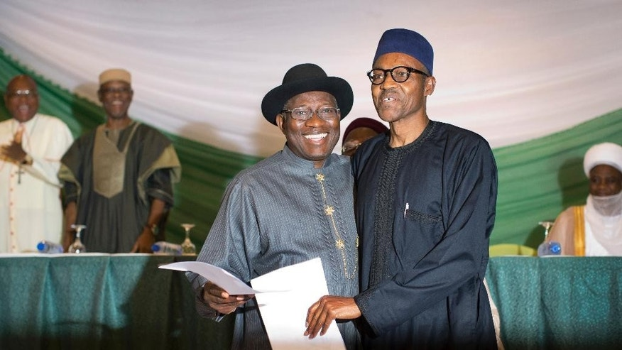 "Nigeria's President Goodluck Jonathan, center-left, and opposition candidate Gen. Muhammadu Buhari, center-right, hug and shake hands after signing a renewal of their pledge to hold peaceful ""free, fair, and credible"" elections, at a hotel in the capital Abuja, Nigeria Thursday, March 26, 2015. Nigerians are due to go to the polls to vote in presidential elections on Saturday. (AP Photo/Ben Curtis)"