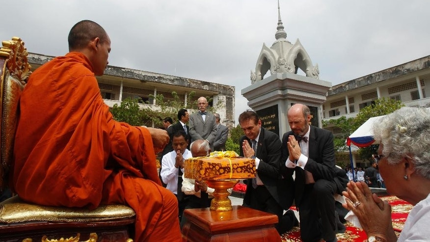 German Ambassador to Cambodia, Joachim Baron Von Marschall, second from right, prays a Buddhist monk, left, during an opening ceremony of the Memorial in Tuol Sleng Genocide Museum in Phnom Penh, Cambodia, Thursday, March 26, 2015. The memorial built at Toul Sleng Genocide Museum to remember at least 12,000 people tortured and killed there during the radical Khmer Rouge regime, has been official inaugurated Thursday. (AP Photo/Heng Sinith)