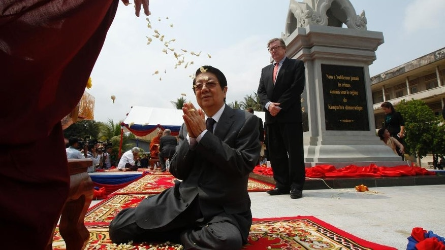 Cambodian Deputy Prime Minister Sok An, center, prays a Buddhist monk, left, during an opening ceremony of the Memorial in Tuol Sleng Genocide Museum in Phnom Penh, Cambodia, Thursday, March 26, 2015. The memorial built at Toul Sleng Genocide Museum to remember at least 12,000 people tortured and killed there during the radical Khmer Rouge regime, has been official inaugurated Thursday. (AP Photo/Heng Sinith)