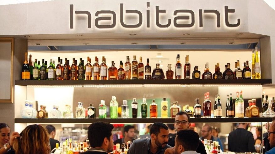 In this Monday, March 23, 2015 photo, customers order at the Habitant Restaurant inside Nordstrom, inside the newly built, The Mall of San Juan, in San Juan, Puerto Rico. Many Puerto Ricans do seem to have been busy shopping while the government struggles with $73 billion in public debt and U.S. investors worry some of island's public agencies could go bankrupt. (AP Photo/Ricardo Arduengo)