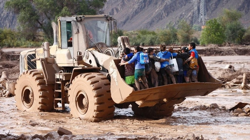 A group of people is transported across a mud covered area on the shovel of a front-end loader after flooding from heavy rains in Copiapo, Chile, Thursday, March 26, 2015. Unusually heavy thunder storms and torrential rains that began on Tuesday have blocked roads, caused power outages and affected some 600 people on this normally dry region. CHILE OUT - NO USAR EN CHILE (AP Photo/Aton Chile, Adrian Aylwin)