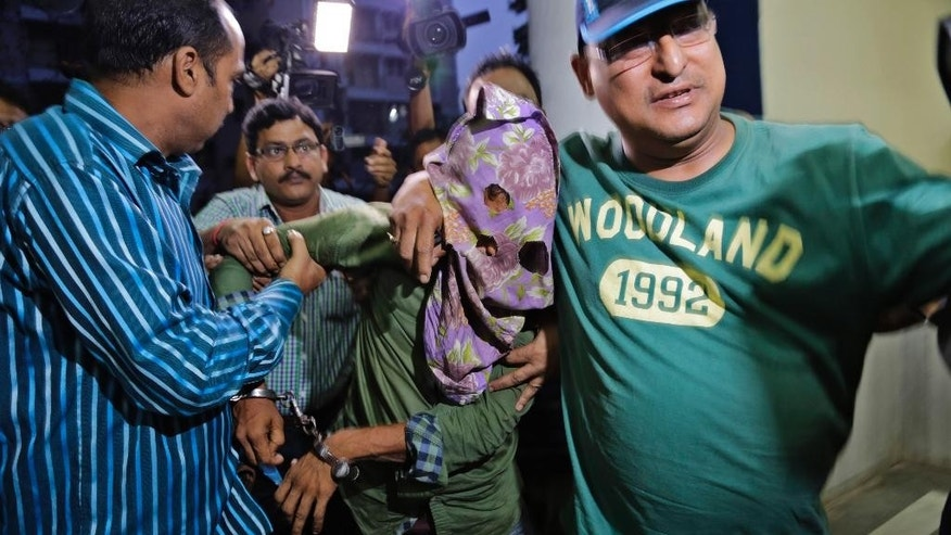 Mohammad Salim Shaikh, one of the two suspects arrested by police in the gang rape of an elderly nun in in a missionary school in eastern India nearly two weeks ago, is brought to the Crime Investigation Department office in Kolkata, India, Thursday, March 26, 2015. A police officer says the suspects were arrested Thursday after a nationwide hunt. The nun, in her 70s, was hospitalized in serious condition. She has since recovered and left the hospital. (AP Photo/Bikas Das)