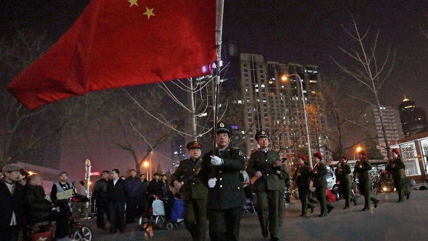 In this Tuesday, March 24, 2015 photo, a Chinese man holding a national flag leads his members of friend with toy guns dance to a revolutionary song during their daily exercises at a square outside a shopping mall in Beijing. This group is a part of senior health trend that has filled squares and apartment courtyards across China, winning the admiration of medical experts but upsetting neighbors over the noise level. (AP Photo/Andy Wong)