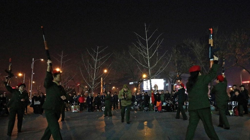 In this Tuesday, March 24, 2015 photo, Chinese women holding toy guns dance to a revolutionary song during their daily exercises at a square outside a shopping mall in Beijing. This group is a part of senior health trend that has filled squares and apartment courtyards across China, winning the admiration of medical experts but upsetting neighbors over the noise level.(AP Photo/Andy Wong)