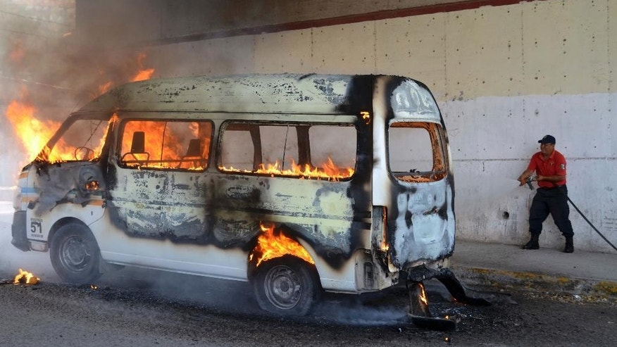 An emergency worker tries to extinguish a burning passenger van after protesters set it ablaze in the city of Chilpancingo, Mexico, Thursday, March 26, 2015. Protesters marked the six-month anniversary of the disappearance of 43 students with marches in Mexico City and other cities in Mexico and asked that elections scheduled for June in the southwestern state of Guerrero be suspended. Federal investigators say local police handed the students over to a drug gang, which killed them and incinerated their remains. Nearly 100 people have been detained in the case. (AP Photo/Alejandrino Gonzalez)