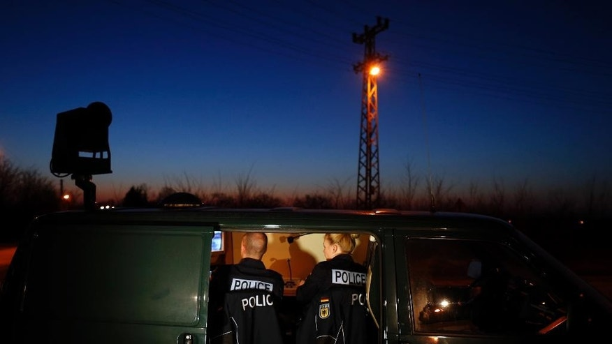 FILE - In this Feb 13, 2015 file photo members of the German border police sit in a van as they check a security camera while monitoring a stretch of the Serbian border with Hungary in the village of Hajdukovo, some 180 kilometers north of Belgrade, Serbia. Some 20 German police officers, equipped with vehicles with thermal vision cameras, joined Serbian security forces on Serbia's border with Hungary on Friday to try to halt a torrent of migrants. (AP Photo/Darko Vojinovic)