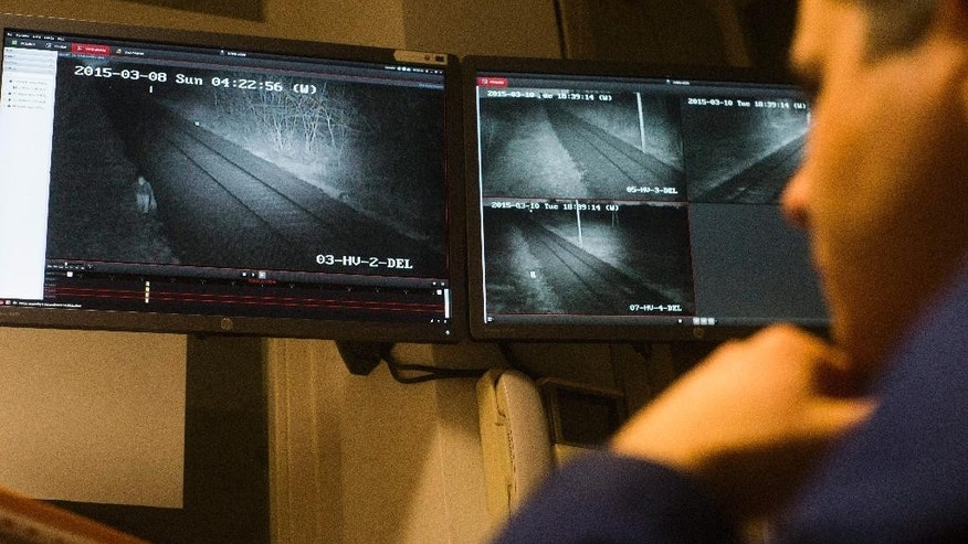 The March 10, 2015 photo shows police officer Laszlo Aradszky monitoring the moving of the migrants by thermal camera in the border station in Kelebia, a border crossing on the Serbian border, 177 kms south of Budapest, Hungary. From Greece to Hungary via Macedonia and Serbia is the fastest-growing smuggling route for migrants trying to get illegally into the European Union.   (AP Photo/MTI,Zoltan Balogh)