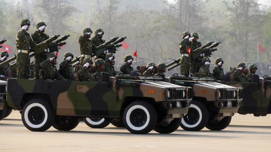 "Myanmar military soldiers salute from vehicles as they leave the venue during a ceremony to mark the 70th anniversary Armed Forces Day, in Naypyitaw, Myanmar, Friday, March 27, 2015. Myanmar's powerful military commander pledged Friday to work to support successful elections in November, calling it ""an important landmark for democracy implementation,"" and warned that the army will not tolerate instability or armed threats. (AP Photo/Khin Maung Win)"