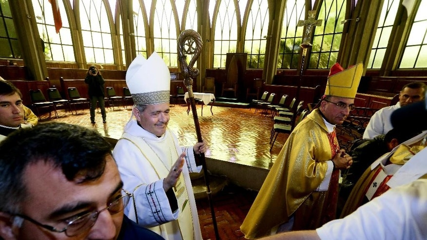 FILE -- In this  March 21, 2015 file photo, Rev. Juan Barros, center, leaves after his ordination ceremony as bishop in Osorno, southern Chile. Several members of Pope Francis' sex abuse advisory board are expressing concern and incredulity over his decision to appoint the Chilean bishop to a diocese despite allegations that he covered up for Chile's most notorious pedophile. In interviews and emails with The Associated Press, the experts have questioned Francis' pledge to hold bishops accountable and keep children safe, given the record of Bishop Juan Barros in the case of the Rev. Fernando Karadima. The five commission members spoke to the AP in their personal and professional capacity and stressed that they were not speaking on behalf of the commission, which Francis formed in late 2013 and named Boston Cardinal Sean O'Malley to head. (AP Photo/Mario Mendoza Cabrera) CHILE OUT - NO USAR EN CHILE