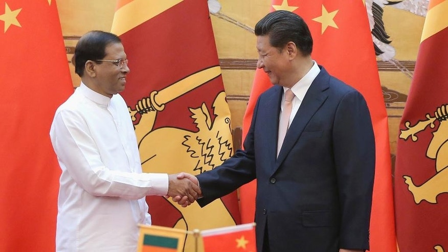 Sri Lankan President Maithripala Sirisena, left, shakes hands with Chinese President Xi Jinping during a signing ceremony in the Great Hall of the People Thursday, March 26, 2015 in Beijing, China. Sri Lanka's new president held talks with Xi amid a push to recalibrate his predecessor's strongly pro-China policies and a review of major Chinese projects in the island nation. (AP Photo/Feng Li, Pool)