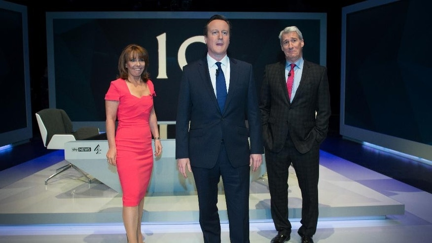 Britain's Prime Minister David Cameron, center, stands with Jeremy Paxman, right, and Kay Burley ahead of the TV interview in west London, Thursday March 26, 2015. Conservative leader Cameron went first in the show Thursday night, facing harsh questions from prominent TV journalist Jeremy Paxman. Miliband, the Labour Party leader, was set to follow, they weren't expected to share a stage at the studio. (AP Photo/Stefan Rousseau, Pool)