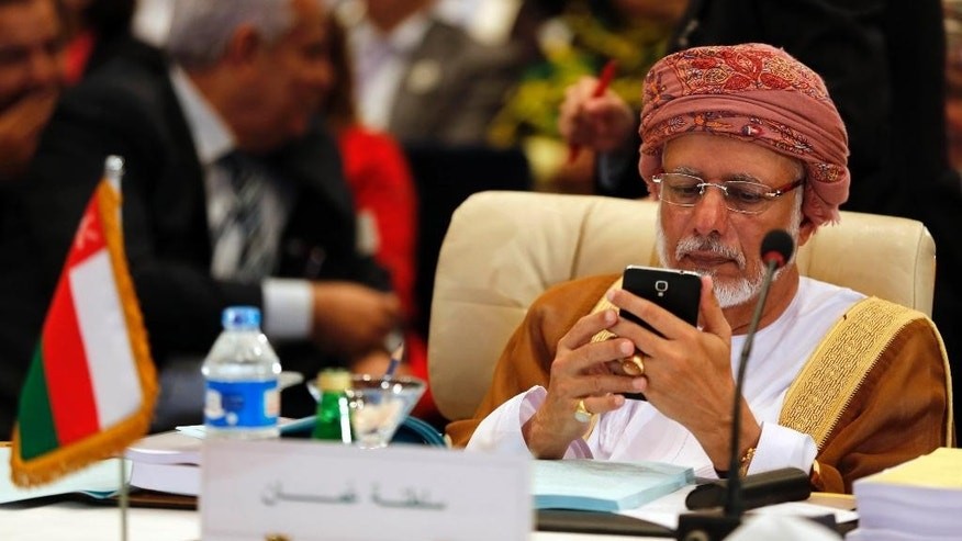 Omani Foreign Minister Yusuf Bin Alawi bin Abdullah looks at his phone during a meeting of Arab foreign ministers in Sharm el Sheik, South Sinai, Egypt, Thursday, March 26, 2015. (AP Photo/Amr Abdallah Dalsh, Pool)