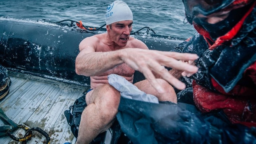 In this Feb. 19, 2015 photo, provided by 5 Swims Expedition, Lewis Pugh, of the United Kingdom, is helped onto a support boat in the Ross Sea in Antarctica. An extreme swimmer from Britain, Pugh completed the last of four swims in the ocean near Antarctica this month, including two that were further south than anybody had ever swum before. (AP Photo/Kelvin Trautman)