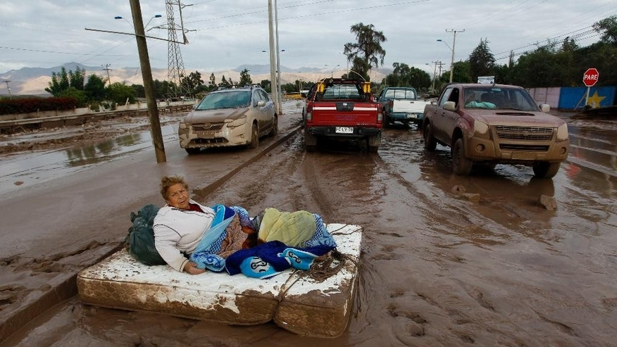 A woman rests on a mattress on a mud covered street after rains caused heavy flooding in Copiapo, Chile, Thursday, March 26, 2015. Unusually heavy thunder storms and torrential rains that began on Tuesday have blocked roads, caused power outages and affected some 600 people on this normally dry region. (AP Photo/Aton Chile, Marcelo Hernandez) - CHILE OUT - NO USAR EN CHILE