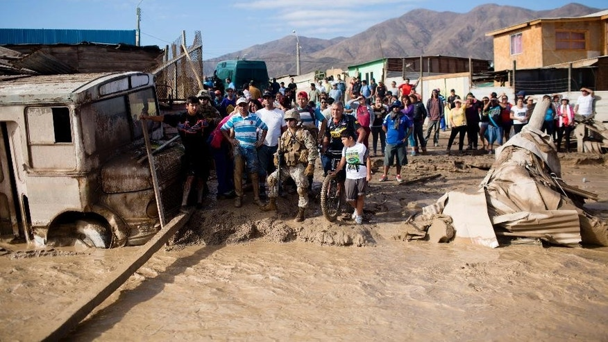 People stand on the edge of a mud covered street in Chanaral, Chile, Friday, March 27, 2015. Unusually heavy thunder storms, torrential rains and overflowing rivers that began on Tuesday left tons of mud covering communes of northern Chile desert, that left at least nine dead and villages without water, electricity or communications. (AP Photo/Pablo Sanhueza) CHILE OUT - NO USAR EN CHILE