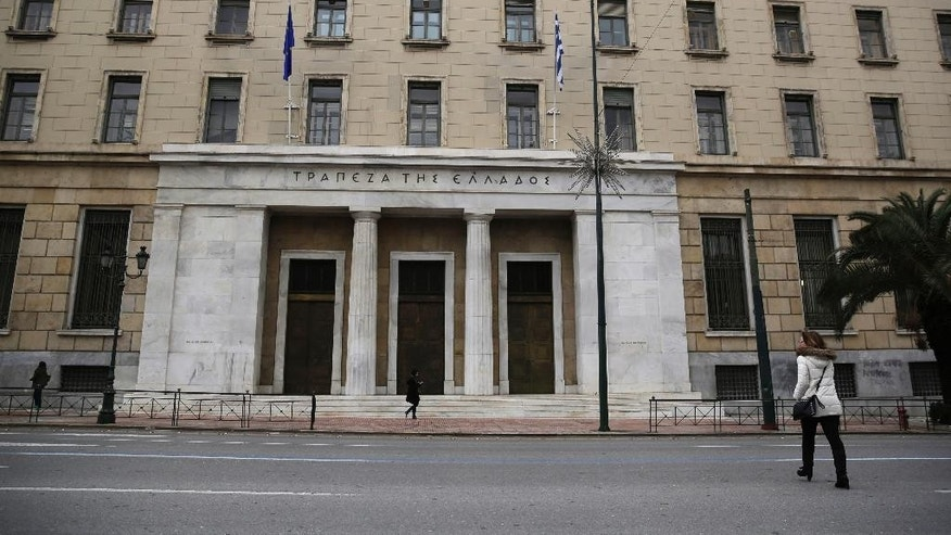People walk past the Bank of Greece headquarters, in central Athens, on Friday, March 27, 2015. Greek bank deposits dropped by more than 7.5 billion euros ($8.2 billion) in February, ramping up pressure on the country's teetering financial system as its government scrambles to reach a deal with creditors within days. (AP Photo/Petros Giannakouris)