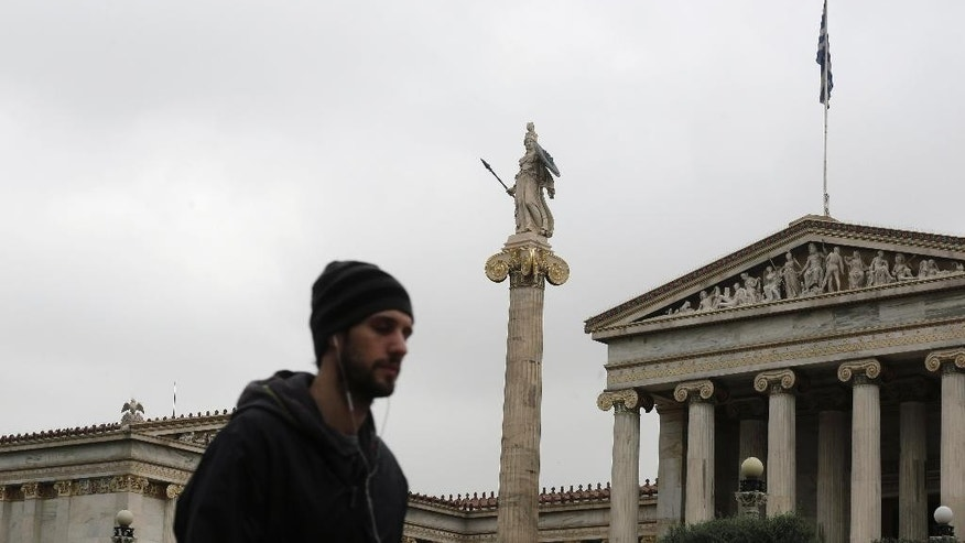 A man walks past  the Athens Academy with  the 19th century statue of the ancient goddess Athena, on Friday, March 27, 2015. Greek bank deposits dropped by more than 7.5 billion euros ($8.2 billion) in February, ramping up pressure on the country's teetering financial system as its government scrambles to reach a deal with creditors within days. (AP Photo/Petros Giannakouris)