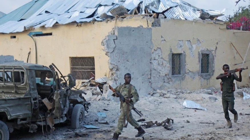 Somali soldiers take position after a bomb that was detonated at the gate of one of Mogadishu's most popular hotel. Friday, March, 27, 2015, A Somali police official says a suicide bomber has detonated his explosives-laden car at the gate of a hotel popular with government officials in Mogadishu. Capt. Mohamed Hussein says gunfire could be heard inside the Maka-Mukarramah Hotel, but it was not clear if any gunmen had managed to penetrate the hotel's gate( AP P hoto/Farah Abdi Warsameh)
