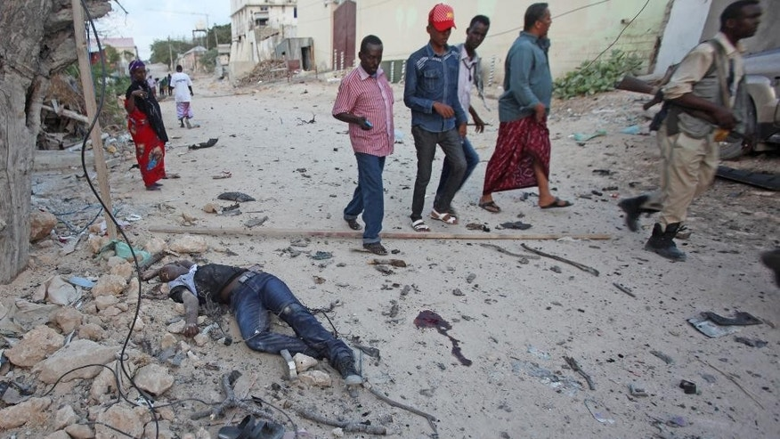 Somalis walk past a dead  civilian  outside the hotel who was killed  after a car bomb that was detonated at the gate of a hotel in Mogadishu, Somalia , Friday, March, 27, 2015,, A Somali police official says a suicide bomber has detonated his explosives-laden car at the gate of a hotel popular with government officials in Mogadishu. Capt. Mohamed Hussein says gunfire could be heard inside the Maka-Mukarramah Hotel, but it was not clear if any gunmen had managed to penetrate the hotel's gate( AP Photo/Farah Abdi Warsameh)