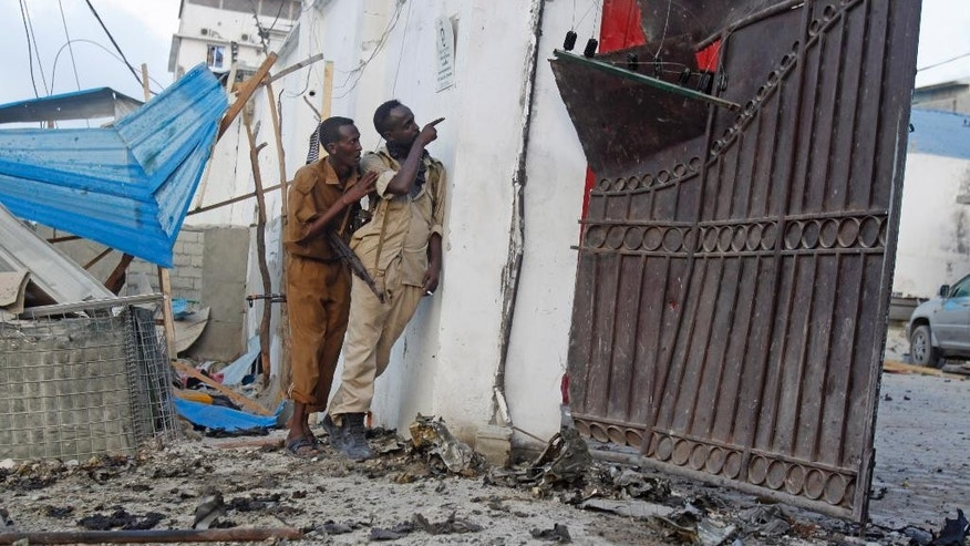 Somali soldiers take position after an attack on a hotel in Mogadishu Somalia, Friday, March, 27, 2015, a Somali police official says a suicide bomber has detonated his explosives-laden car at the gate of a hotel popular with government officials in Mogadishu. Capt. Mohamed Hussein says gunfire could be heard inside the Maka-Mukarramah Hotel, but it was not clear if any gunmen had managed to penetrate the hotel's gate. (AP Photo/Farah Abdi Warsameh)