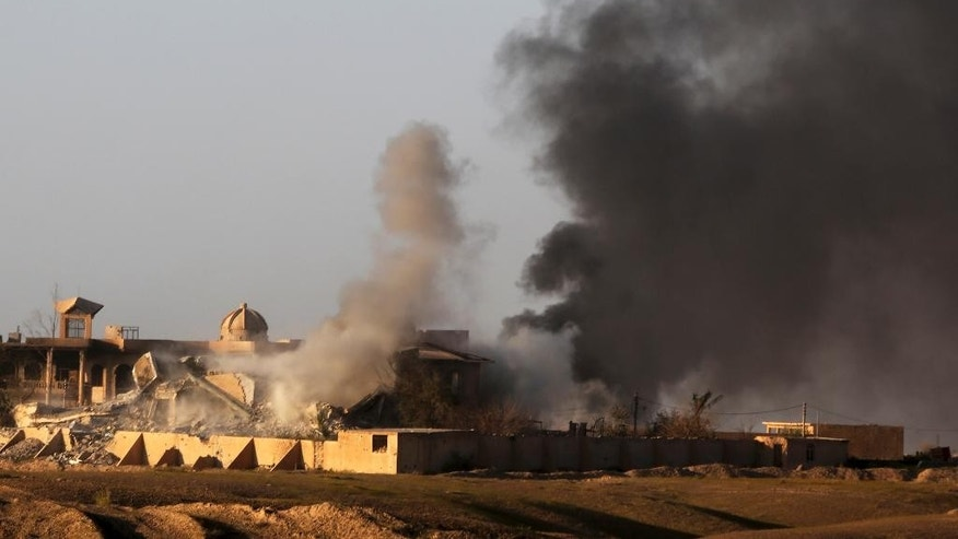 Smoke rises from buildings in central Tikrit, Iraq, during clashes between Iraqi security forces and Islamic State group extremists in the city, 130 kilometers (80 miles) north of Baghdad, Iraq, Thursday, March 26, 2015. Iraqi troops started the final phase of an offensive to recapture Saddam Hussein's hometown of Tikrit on Thursday, a military official said, just hours after the United States launched airstrikes on the Islamic State held city. (AP Photo/Khalid Mohammed)