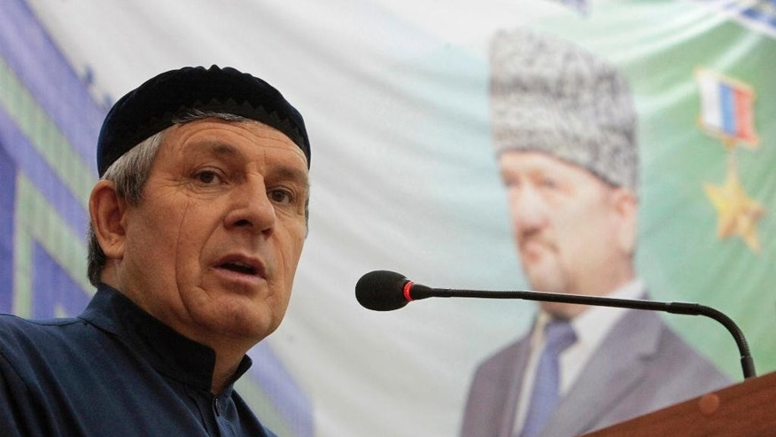 In this photo taken Friday, March 20, 2015 speaker of Chechnya's regional legislature Dukuvakha Abdurakhmanov speaks in Chechnya's provincial capital Grozny, Russia. Abdurakhmanov has called for encouraging separatism in U.S. states near the border with Mexico if Washington provides Ukraine with lethal arms, a statement quickly disavowed by the Kremlin. In the background is a portrait of Akhmad Kadyrov, the Chechen president who was assassinated in a 2004 bomb blast. (AP Photo/Musa Sadulayev)