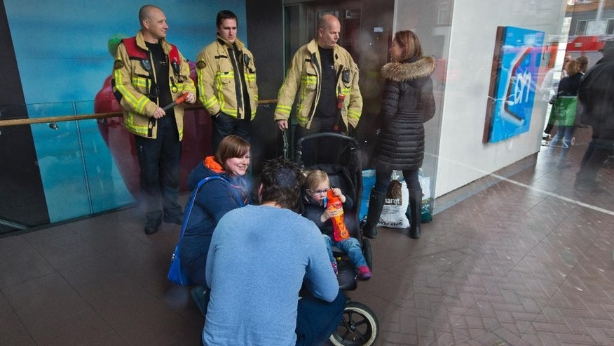 A couple comforts a young girl in a stroller after being freed from an elevator by the fire department, rear, during a power outage in Amsterdam, Netherlands, Friday, March 27, 2015. The Dutch capital Amsterdam and surrounding towns suffered a major power outage, halting trains, trams and affecting flights to Schiphol Airport. (AP Photo/Peter Dejong)