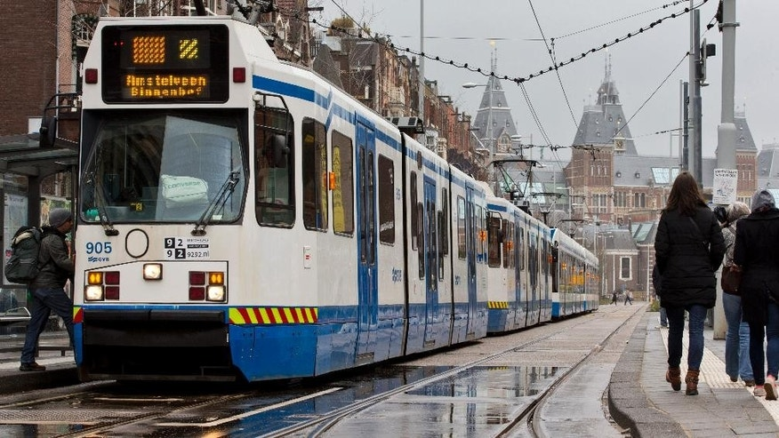 A line of trams stands immobilized near Rijksmuseum, rear, in Amsterdam, Netherlands, Friday, March 27, 2015. The Dutch capital Amsterdam and surrounding towns suffered a major power outage, halting trains, trams and affecting flights to Schiphol Airport.(AP Photo/Peter Dejong)